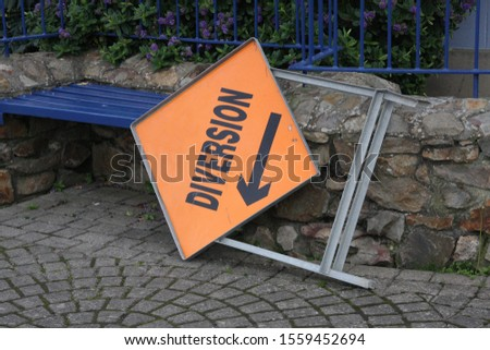 closeup of black lettering diversion on vivid orable metal sign with direction arrow pointing downwards