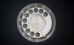 Closeup of black retro vintage telephone with rotary dialer or dialpad. Local vintage telephone for background with copyspace. Rotary dialpad telephone.