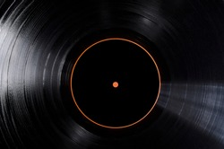 Closeup of black vinyl record and black lable of it as a background