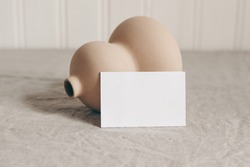 Closeup of blank business card and modern organic shaped ceramic vase on beige linen tablecloth. Empty paper card mockup scene in neutral colors. Art, concept. Sparse composition Blurred background.