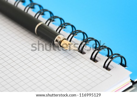 Closeup of blank open spiral notebook and fountain pen. Good background