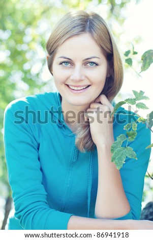 Closeup of blue-eyed smiling woman against blurred background outdoors with selective focus