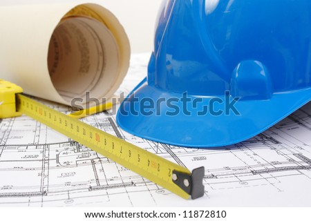 Closeup of blue hard hat, yellow pencil, measuring tape and building plans