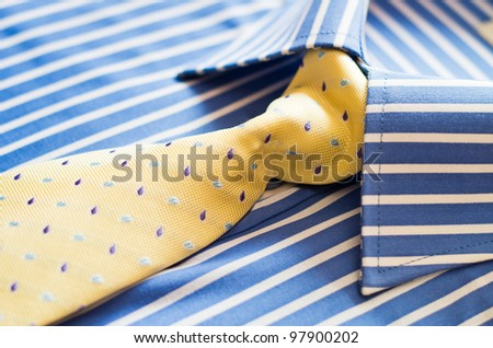 closeup of blue shirt with stripes and yellow tie
