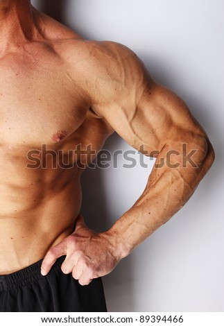 Closeup of body builders arm, isolated on grey