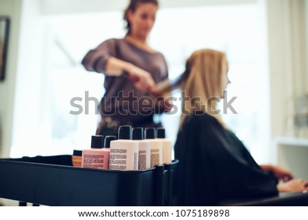 Closeup of bottles of shampoo and conditioner on a tray in a hair salon with a hairdresser straightening a client's hair in the background