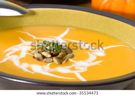 Closeup of bowl of hot delicious pumpkin soup garnished with cream, roasted pumpkin seeds and fresh thyme