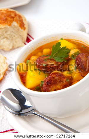 Closeup of bowl of hot fresh golden chorizo and chickpea soup and cheese garlic buns