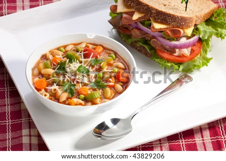 Closeup of bowl of hot fresh Minestrone soup and whole wheat bread turkey breast sandwich
