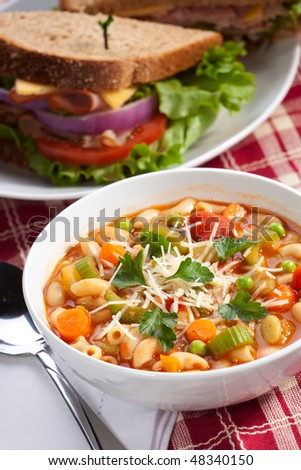 Closeup of bowl of hot fresh Minestrone soup and whole wheat bread turkey breast sandwich - stock photo