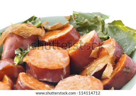 Closeup of bowl of red yams with broccoli and kelp on white background