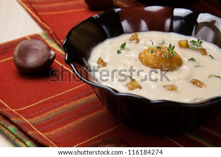 Closeup of bowls of hot chestnut kohlrabi soup with thyme and caramelized chestnut.