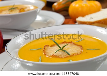 Closeup of bowls of hot delicious pumpkin soup with roasted apples, and rosemary.
