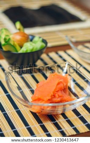 Closeup of bowls with salmon, avocado and cucumber cut ready to prepare sushi