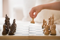 Closeup of Boy's hand holding chess figure while playing chess in the room. Little clever child playing chess at home. Education concept.