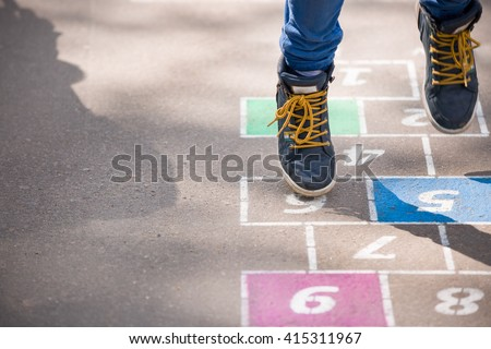 Closeup of boy\'s legs and hopscotch drawn on asphalt. Child playing hopscotch on playground outdoors on a sunny day. outdoor activities for children.