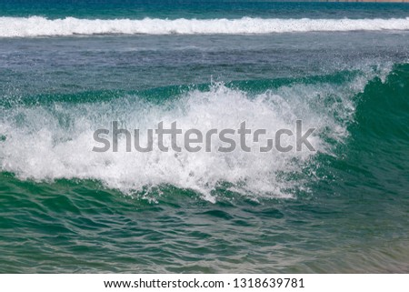 Closeup of breaking wave with another wave in the background #1318639781