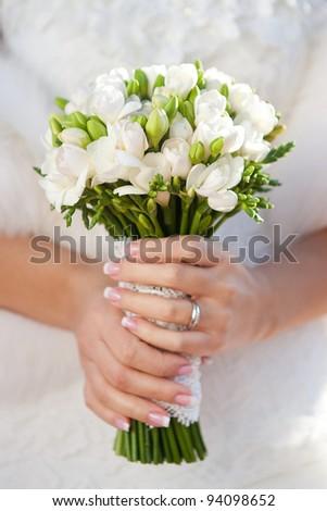 closeup of bride hands holding beautiful wedding bouquet