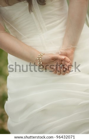 Closeup of bride's hands on wedding dress outside