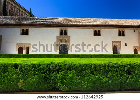 Closeup of bright green garden hedges and white walls and arches