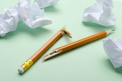 Closeup of broken pencil and crumpled paper on the green surface.Concept of emotional stress