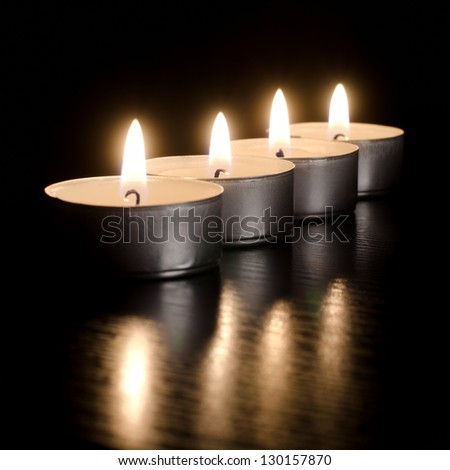 Closeup of burning candles on a black background