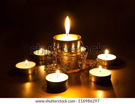 Closeup of burning candles on dark background