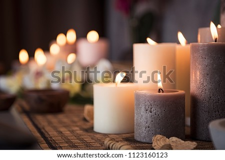 Photo of  Closeup of burning candles spreading aroma on table in a spa room. Beautiful composition with grey and white candles for spa treatment. Zen and relax concept.