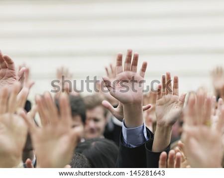 Closeup of business crowd raising hands