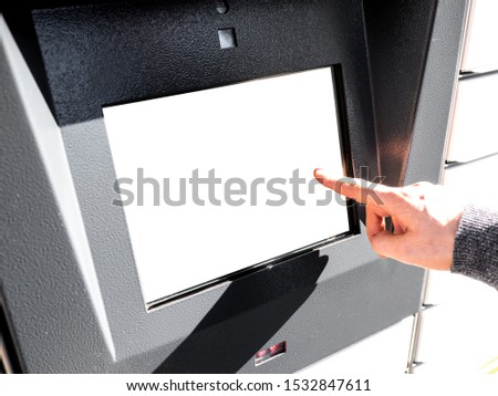 Closeup of business man hand using kiosk Electronic Locker, Yellow automated parcel terminal (parcel locker, post terminal, E-Locker) on the street with empty screen for mockup, home delivery.