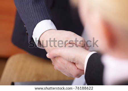 Closeup of business people shaking hands over a deal