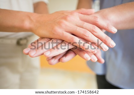 Closeup of business people stacking hands in office