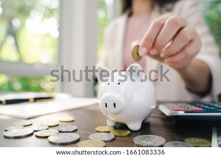 Closeup of business woman hand putting money coin into piggy bank for saving money. saving money and financial concept