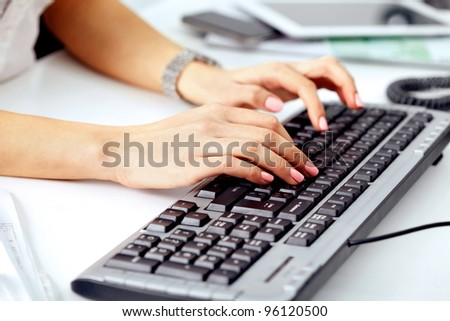 Closeup of business woman's hand typing on computer keyboard
