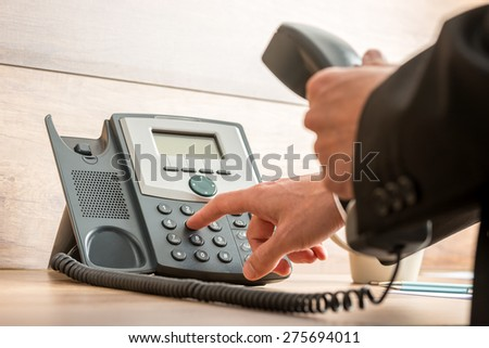 Closeup of businessman hand holding a landline telephone receiver dialing a phone number in order to make a call.