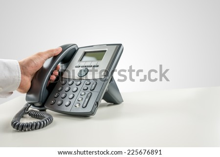 Closeup of businessman making a phone call on landline telephone. Conceptual of customer service or telemarketing.
