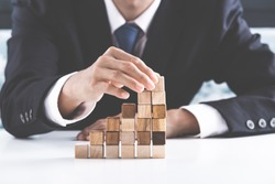 Closeup of businessman making a pyramid with empty wooden cubes