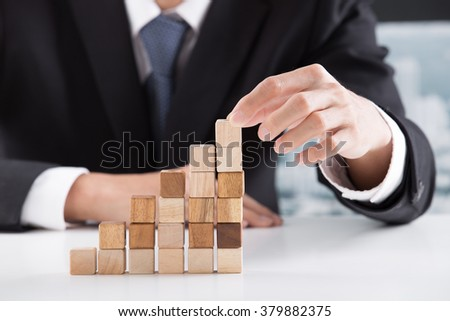 Closeup of businessman making a pyramid with empty wooden cubes - Shutterstock ID 379882375