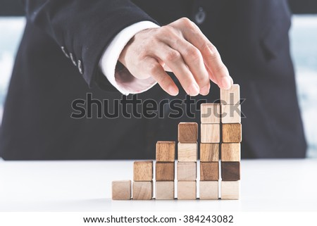 Closeup of businessman making a pyramid with empty wooden cubes - Shutterstock ID 384243082