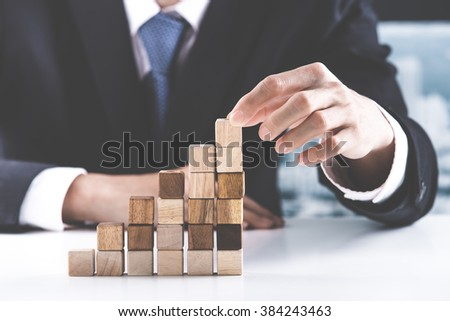 Closeup of businessman making a pyramid with empty wooden cubes - Shutterstock ID 384243463