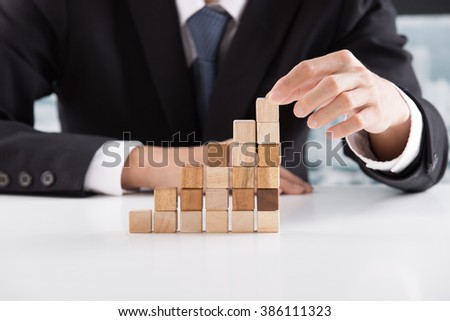 Closeup of businessman making a pyramid with empty wooden cubes - Shutterstock ID 386111323