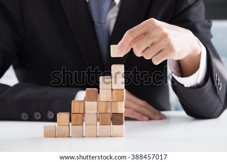 Closeup of businessman making a pyramid with empty wooden cubes - Shutterstock ID 388457017