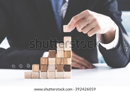 Closeup of businessman making a pyramid with empty wooden cubes - Shutterstock ID 392426059