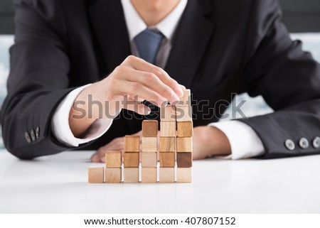 Closeup of businessman making a pyramid with empty wooden cubes - Shutterstock ID 407807152