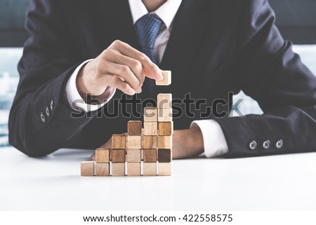 Closeup of businessman making a pyramid with empty wooden cubes - Shutterstock ID 422558575