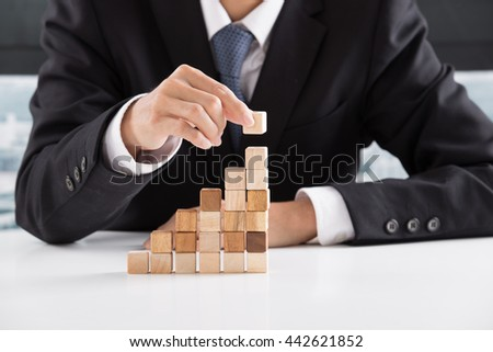 Closeup of businessman making a pyramid with empty wooden cubes - Shutterstock ID 442621852