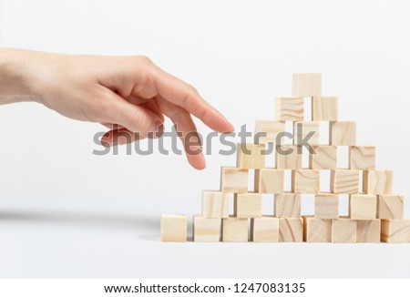 Closeup of businessman making a pyramid with empty wooden cubes. Concept of business hierarchy. #1247083135
