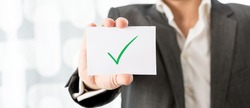 Closeup of businessman or teacher holding up a white card with green check mark. Conceptual of successfully completed task or homework.
