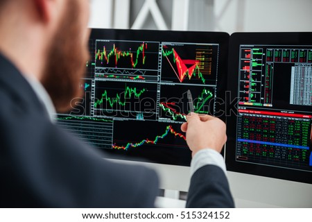 Closeup of businessman pointing on monitor of computer with charts and graphs in office