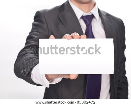Closeup of businessman's hand holding up card on white background
